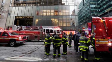 Kendaraan dan para petugas pemadam berada di lokasi kebakaran di Fifth Avenue, depan Trump Tower, di New York, Senin (8/1). Kebakaran yang mengakibatkan dua orang luka-luka tersebut berasal dari pendingin di bagian atas gedung. (AP Photo/Richard Drew)