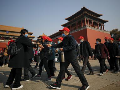 Turis mengenakan masker untuk mencegahn penyebaran virus corona hingga memasuki Kota Terlarang di Beijing (25/10/2020). Dengan wabah COVID-19 yang sebagian besar terkendali di dalam perbatasan China, rutinitas kehidupan sehari-hari yang normal telah mulai kembali untuk warganya. (AP Photo/Andy Wong)