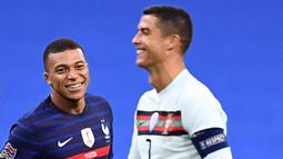 Striker Prancis, Kylian Mbappe, tersenyum kepada striker Portugal, Cristiano Ronaldo, pada laga UEFA Nations League di Stadion Stade de France, Senin (12/10/2020). Kedua tim bermain imbang 0-0. (AFP/Franck Fife)