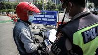 Polisi memeriksa surat-surat pengendara motor saat penyekatan PPKM Darurat di kawasan Ratu Plaza, Jakarta, Sabtu (17/7/2021). Menko PMK Muhadjir Effendy menerangkan perpanjangan PPKM Darurat untuk menekan penularan COVID-19 sudah diputuskan Presiden RI Joko Widodo. (Liputan6.com/Faizal Fanani)