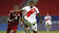 Bek timnas Peru, Miguel Araujo mengontrol bola dibayangi penyerang Venezuela, Sergio Cordova pada laga terakhir penyisihan Grup B  Copa America 2021 di Estadio Nacional Mane Garrincha, Minggu (27/6/2021). Menghadapi Venezuela, Peru menang tipis dengan skor 1-0. (SILVIO AVILA / AFP)