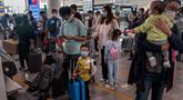 """Orang-orang mengantre check-in untuk penerbangan domestik menjelang liburan """"Golden Week"""" di Bandara Internasional Ibu Kota Beijing pada 30 September 2020. Gelombang liburan melanda China yang warganya merayakan libur panjang, yang dikenal dengan Golden Week. (NICOLAS ASFOURI / AFP)"""
