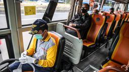 Penumpang berada di bus sekolah di Kawasan Stasiun Sudirman, Jakarta, Jumat (19/6/2020). 50 armada bus sekolah ditempatkan di lima stasiun, yakni Tanah Abang, Manggarai, Juanda, Sudirman dan Tebet. (Liputan6.com/Faizal Fanani)