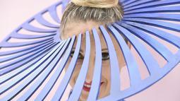 Seorang wanita mengenakan topi unik sebelum pertandingan pacuan kuda Piala Melbourne di Melbourne (5/11/2019). Para wanita tampil cantik dan modis dengan hiasan kepala yang mereka gunakan selama menyaksikan balap kuda di Melbourne Cup.  (AFP Photo/William West)