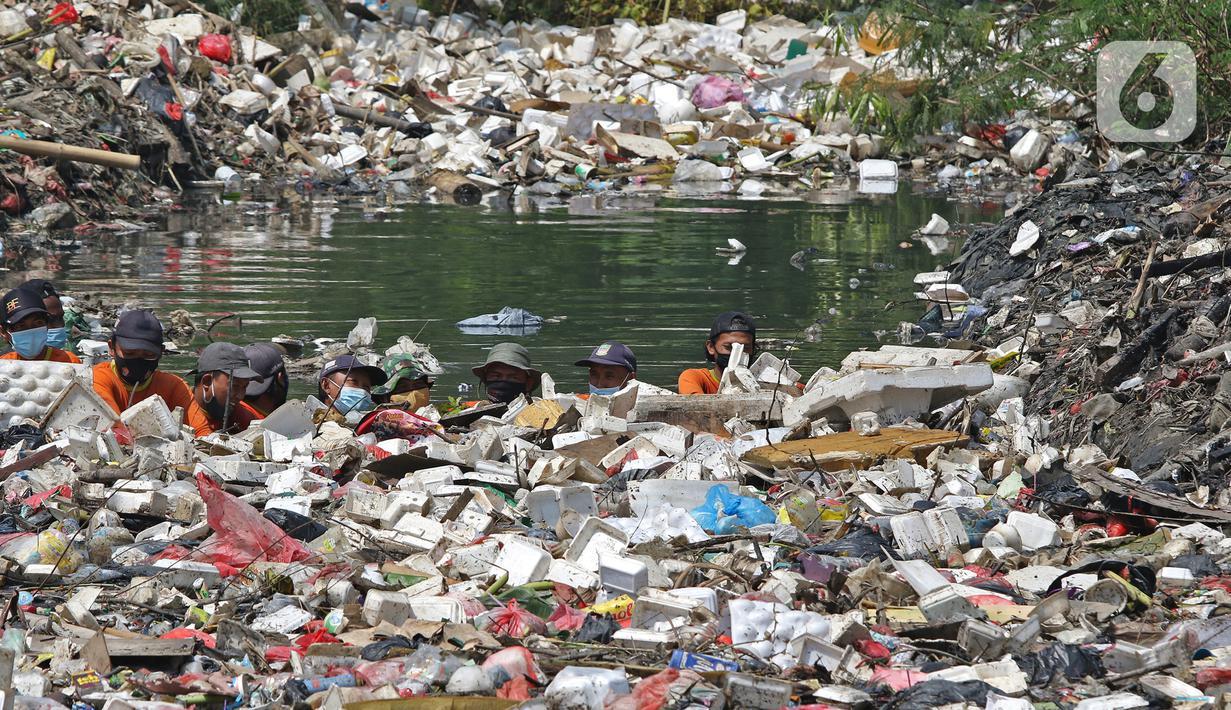 Sejumlah petugas DLH mendorong sampah yang memenuhi Kali Busa untuk dikeruk menggunakan ekskavator di Tambun Utara, Kabupaten Bekasi, Jawa Barat, Jumat (10/9/2021). Pengerukan sampah ditargetkan selesai selama dua hari dan selanjutnya dipindahkan ke TPA Burangkeng. (Liputan6.com/Herman Zakharia)