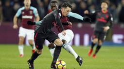 Pemain Arsenal, Mesut Ozil (kiri) berusaha melewati adangan pemain West Ham, Pedro Obiang pada lanjutan Premier League di London stadium, London, (13/12/2017). Arsenal bermain imbang 0-0 dengan West Ham. (AP/Kirsty Wigglesworth)