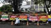 Pemulung berjalan melewati karangan bunga di depan Gedung KPU, Jakarta, Sabtu (21/4). Karangan bunga di depan Gedung KPU terus bertambah setiap harinya. (Liputan6.com/JohanTallo)