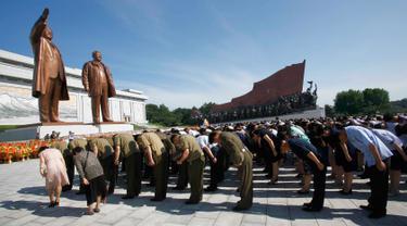 Warga dan tentara memberi penghormatan kepada patung mendiang pemimpin Kim Il Sung dan Kim Jong Il di Bukit Mansu, Pyongyang, Korea Utara, Senin (8/7/2019). Warga Korea Utara tengah memperingati 25 tahun meninggalnya Kim Il Sung. (AP Photo/Jon Chol Jin)