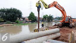 Alat berat saat memasang Tiang Proyek jalan tol Becakayu di Jalan kali malang, Jakarta, Sabtu (28/5) Proyek tol yang sempat mangkrak ini terus di percepat pembangunanya dan di targetkan akhir 2017 akan rampung. (Liputan6.com/Helmi Affandi)