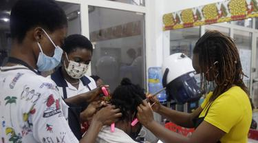 Penata rambut, memakai masker menata rambut pelanggan di dalam salon di Lagos, Nigeria, Rabu (26/5/2021). Salon tersebut menerapkan protokol kesehatan untuk para penata rambutnya saat melayani pelanggan untuk menghindari penyebaran virus Covid-19. (AP Photo/Sunday Alamba)