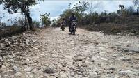 Seorang warga melintas di jalan rusak di Dusun Bulu Barat Desa Batuputih Daya, Senin (12/11). (Ubay Shabaro/RadarMadura.id)