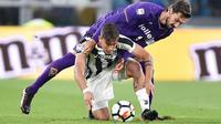 Pemain Juventus, Paulo Dybala (bawah) berebut bola dengan pemain Fiorentina, Davide Astori pada  lanjutan Serie A di Allianz Stadium, Turin, (20/9/2017). Juventus menang 1-0. (Alessandro Di Marco/ANSA via AP)