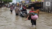 Seorang nenek digendong saat melintasi banjir yang menggenangi Jalan KH Hasyim Ashari, Tangerang, Banten, Kamis (2/1/2020). Banjir yang menggenangi jalan penghubung Jakarta- Tangerang tersebut mulai surut dan sudah bisa dilintasi pejalan kaki. (Liputan6.com/Angga Yuniar)