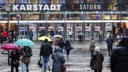 Orang-orang berjalan ke pusat perbelanjaan di pusat Kota Essen, Jerman, Senin (14/12/2020). Jerman melakukan lockdown nasional pada 16 Desember 2020 untuk memerangi pandemi COVID-19. (AP Photo/Martin Meissner)