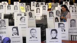 Seorang wanita berdiri diantara deretan tempat duduk  yang disertai foto para selebriti dan tamu saat persiapan jelang Screen Actors Guild Awards 2016 di Shrine Auditorium, Los Angeles, Jumat (29/1). (REUTERS/Mario Anzuoni)
