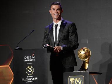 Striker Juventus, Cristiano Ronaldo memberi sambutan usai meraih Penghargaan Pemain Terbaik Tahun 2018 selama Dubai Globe Soccer Awards ke-10 di Dubai (3/1). Ronaldo mengungguli Antoine Griezmann dan Kylian Mbappe. (AFP Photo/Fabio Ferrari)