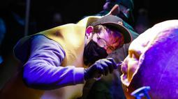 Seorang seniman mengukir labu dalam acara Malam 1.000 Jack-O'-Lantern di Chicago Botanic Garden, Glencoe, Illinois, Amerika Serikat, 24 Oktober 2020. Lebih dari 1.000 labu ukiran tangan dipamerkan di acara tersebut menjelang perayaan Halloween. (Xinhua/Joel Lerner)