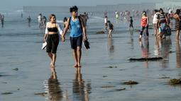 Orang-orang mengunjungi pantai di Playas de Tijuana dekat perbatasan AS-Meksiko di Tijuana Meksiko, Sabtu (3/10/2020). Akhir pekan ini pantai di Playas de Tijuana dibuka kembali dengan pembatasan pengunjung, setelah ditutup sejak Maret lalu guna mencegah penyebaran Covid-19. (Guillermo Arias/AFP)