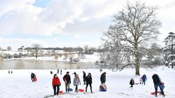 Warga menikmati permainan kereta luncur di taman Dunorlan di Tunbridge Wells (27/2). Cuaca ekstrem yang melanda sebagian wilayah Eropa menyebabkan warga dan wisatawan mengalami sakit dan beberapa meninggal akibat kedinginan. (AFP Photo/Ben Stansall)