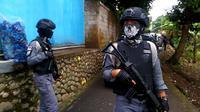 Polisi bersenjata laras panjang berjaga di gang masuk rumah terduga teroris di Pasir Wetan, Banyumas, Sidik. (Foto: Liputan6.com/Muhamad Ridlo)