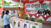 Petugas KPPS melihat warga yang akan memasukkan surat suara dalam kotak di TPS 7 Panggung Lor, Semarang, Jawa Tengah, Rabu (17/4). Para petugas mengenakan pakaian khas Nusantara untuk menghibur dan menarik warga dalam memilih di Pemilu 2019. (Liputan6.com/Gholib)