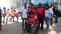 Benny Eka Wijaya (berkursi roda) berfoto di depan Stadion Wibawa Mukti, Cikarang, Selasa (11/9/2018), untuk menyaksikan uji coba Timnas Indonesia melawan Mauritius. (Bola.net/Fitri Apriyani)