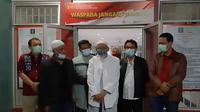 Abu Bakar Baasyir bersama petugas lapas foto bersama setelah dibebaskan dari Lapas Gunung Sindur, Kabupaten Bogor, Jawa Barat, Jumat (8/1/2021). (Handout/Indonesia National Prison/AFP)