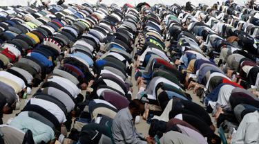Umat muslim melaksanakan salat Jumat di Hagley Park, Kota Christchurch, Selandia Baru, Jumat (22/3). Ibadah itu digelar satu minggu selepas serangan mengerikan terhadap dua masjid di kota Christchurch yang menewaskan 50 orang. (AP/Mark Baker)