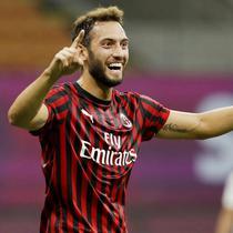 Pemain AC Milan, Hakan Calhanoglu, melakukan selebrasi usai membobol gawang Bologna pada laga Serie A di Stadion San Siro, Sabtu (18/7/2020). AC Milan menang dengan 5-1 atas Bologna. (AP/Luca Bruno)