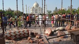 Wisatawan berkumpul di sekitar royal gate atau gerbang kerajaan setelah pilar Taj Mahal runtuh diterpa angin kencang di Agra, India, Kamis (12/4). Dua pilar Taj Mahal yang roboh diterpa angin kencang itu terdapat di gerbang masuk yang berbeda. (AFP Photo)