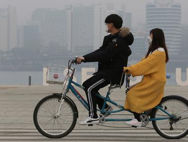 Pasangan naik sepeda menggenakan masker saat pemandangan kota diselimuti kabut tebal partikel debu halus di Seoul, Korea Selatan (5/3). Kementerian Lingkungan Korsel mengeluarkan langkah-langkah penurunan debu halus darurat. (AP Photo/Ahn Young-joon)