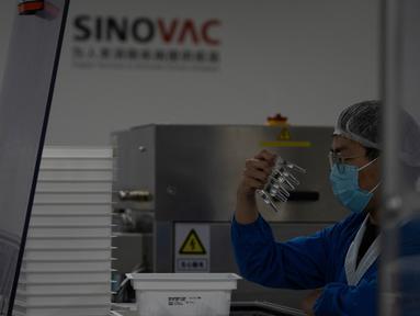Pekerja memeriksa jarum suntik Vaksin CoV-2 SARS untuk COVID-19 yang diproduksi di pabrik vaksin SinoVac di Beijing, Kamis (24/9/2020). Perusahaan farmasi China, Sinovac mengatakan vaksin virus corona yang dikembangkannya akan siap didistribusikan ke seluruh dunia awal 2021. (AP Photo/Ng Han Guan)