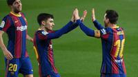 Kapten Barcelona, Lionel Messi (kanan), merayakan gol bersama Pedri (tengah) dan Sergi Roberto setelah membobol gawang Getafe pada lanjutan Liga Spanyol di Camp Nou, Jumat (23/4/2021) dini hari WIB. (AFP/Lluis Gene)