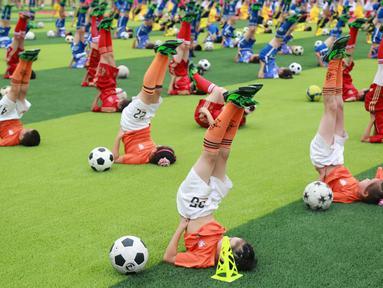 Para siswa beraksi dengan bola saat acara pembukaan sebuah turnamen sepak bola di Dalian, Liaoning, China, (16/7/2016). (Reuters)