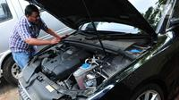 Calon peserta lelang mengecek kondisi mesin mobil hasil sitaan kasus korupsi di Gedung KPK, Jakarta, Selasa (19/9). KPK melelang sebanyak 19 unit mobil dari berbagai model dan merek dengan harga termurah Rp28,8 jutaan. (Liputan6.com/Helmi Afandi)