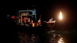 Nelayan Taiwan saat mencari ikan menggunakan api sebagai umpan di perairan New Taipei City, Taiwan, (19/6). Kini Metode tradisional ini hanya digunakan segelintir nelayan dan tersisa tiga kapal saja setiap malam. (REUTERS/Tyrone Siu)