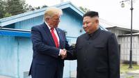 Presiden AS, Donald Trump bertemu dengan Pemimpin Korea Utara, Kim Jong-un di zona demiliterisasi Korea (DMZ), Desa Panmunjom pada Minggu (30/6/2019).  Pertemuan keduanya berawal ketika Trump menuliskan undangan pertemuan dengan Kim melalui Twitter. (AP Photo/Susan Walsh)
