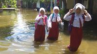 Anak-anak sudah dua minggu ini bersekolah dengan menerjang genangan air banjir. (foto: Liputan6.com / edhie)