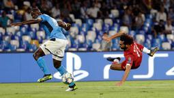 Penggawa Liverpool, Mohamed Salah mencoba mencetak gol saat pemain Napoli, Kalidou Koulibaly berusaha menahan tendangan pada matchday pertama Grup E Liga Champions di Stadion San Paolo, Selasa (17/9/2019). Napoli menundukkan Liverpool 2-0. (AP/Gregorio Borgia)