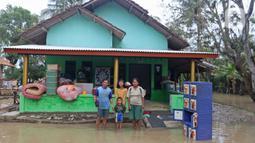 Keluarga Pak Unang berpose di depan kediamannya Desa Sumber Urip Pebayuran, Kabupaten Bekasi, Jawa Barat, Senin (22/2/2021). Banjir merenda keluarga tersebut merapikan barang-barang dan bersihkan rumah yang sudah surut. (Liputan6.com/Herman Zakharia)