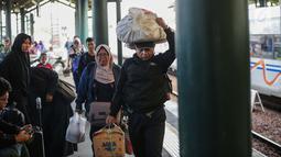 Pemudik mengangkat barang bawaan mereka setibanya dI Stasiun Gambir, Jakarta, Minggu (9/6/2019). Pada H+4 Lebaran yang merupakan puncak arus balik lebaran, sebanyak 78.249 orang tiba di Jakarta melalui Stasiun Gambir sejak 6 Juni 2019 sampai dengan hari ini. (Liputan6.com/Faizal Fanani)