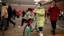 Orang-orang tiba di pintu masuk Kota Terlarang pada hari kedua Tahun Baru Imlek di pintu keluar Kota Terlarang di Beijing (13/2/2021). Tahun Baru Imlek menandai Tahun Sapi pada 12 Februari. (AFP Photo/Noel Celis)