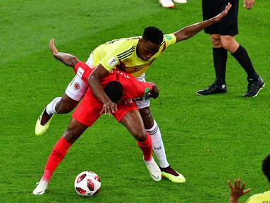 Bek timnas Kolombia, Yerry Mina berebut bola dengan pemain Inggris, Raheem Sterling pada babak 16 besar Piala Dunia 2018 di Stadion Spartak, Selasa (3/7). Selain adu penalti, sebuah kejadian menarik tertangkap kamera pada laga itu. (AFP/Mladen ANTONOV)