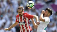 Gelandang Real Madrid Marco Asensio berebut bola dengan bek Atletico Madrid Juanfran saat pertandingan La Liga Spanyol di stadion Santiago Bernabeu di Madrid (8/4). (AFP/Gabriel Bouys)