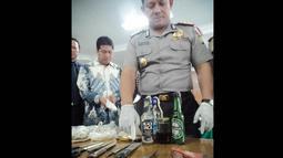 Selain itu, polisi juga mengamankan 22 botol minuman beralkohol, 3 buah bom molotov, 25 botol minuman bir besar, 5 botol minuman bir kecil, 4 buah pisau, kampak, gunting, klemang, 1 kantong plastik sumbu, dan 1 krat botol. (Liputan6.com/Faizal Fanani)