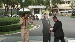 PM Thailand, Prayuth Chan-o-cha dalam konferensi pers saat pengawalnya memasang replika karton bergambar dirinya di Bangkok, Senin (8/1). PM Prayuth kemudian meninggalkan tempat konferensi pers, sementara replikanya berdiri di sana. (TPBS via AP)