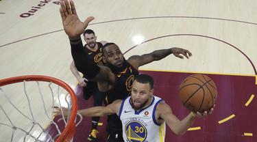 Aksi pemain Warriors, Stephen Curry melakukan tembakan saat diadang pemain Cavaliers, LeBron James pada gim ketiga final NBA basketball di Quicken Loans Arena, (6/6/2018). Warriors kalahkan Cavaliers 110-102. (Gregory Shamus/Pool via AP)