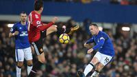 Aksi pemain Everton, Wayne Rooney (kanan) melakukan tembakan melewati adangan pemain Manchester United, Ander Herrera pada lanjutan Premier League di Goodison Park, Liverpool, (1/1/2018). MU menang 2-0. (AFP/Paul Ellis)