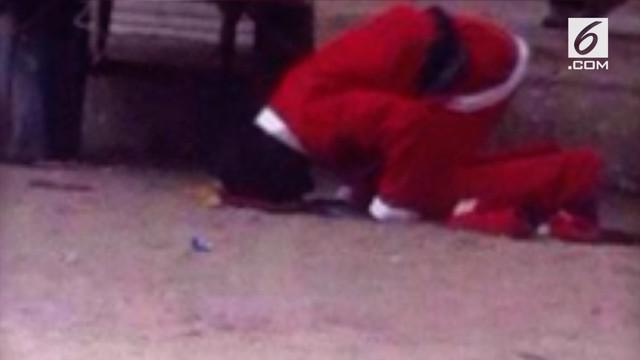 Seorang pria yang menggunakan kostum Sinterklas tepergok warga sedang salat di pinggir jalan.