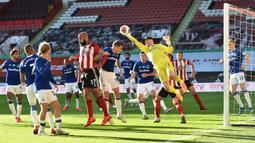 Kiper Everton, Jordan Pickford, berusaha menepis bola saat menghadapi Sheffield United pada laga lanjutan Premier League di Bramall Lane Stadium, Selasa (21/7/2020) dini hari WIB. Everton menang 1-0 atas Sheffield United. (AFP/Peter Powell/pool)